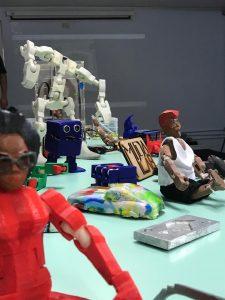 Materiais concretos, como bonecos, estão em cima de uma mesa.