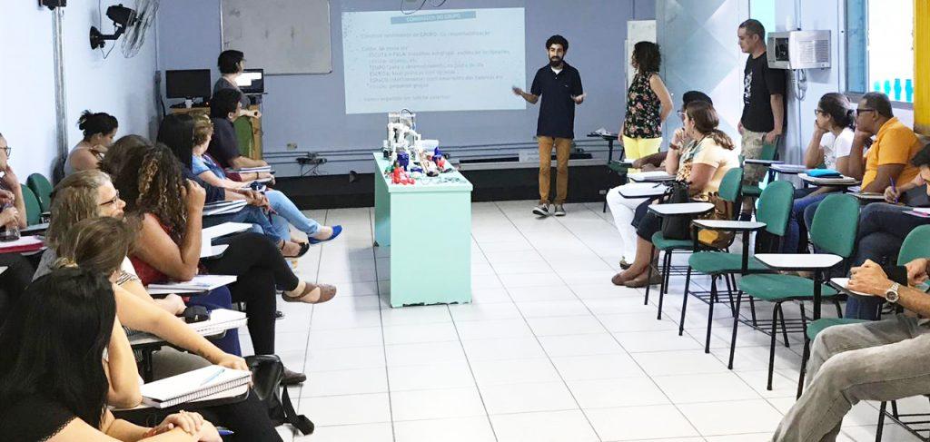 Cinco pessoas em pé na frente da sala de aula. Nas laterais, outras pessoas sentadas em cadeiras.
