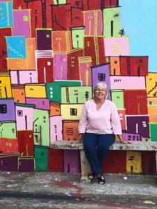 Judith sentada em um banco em frente a uma parede colorida.