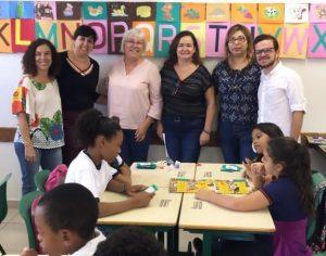 Judith posa para foto com educadoras. Em primeiro plano, crianças sentadas em cadeiras.